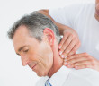 Close-up of a male chiropractor massaging patients neck over whi