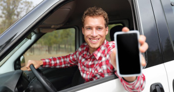 Smartphone man in car driving showing smart phone display smilin
